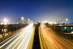Highway at night. A multiple lane highway street on a bridge in an industrial area with trails of headlights and taillights of cars royalty free stock photography