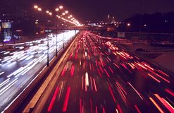 Highway night. Highway near Moscow illuminated by streetlights by a winter evening or night with car streams and buildings far off Royalty Free Stock Photos