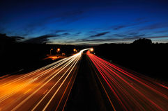 Highway at Night. Headlights and taillights blur, dark blue sky at dusk Royalty Free Stock Photography