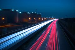 Highway at night. Heavy traffic on a highway. Due to the long exposure time the front and rear lamps of the cars are forimg a white and a red snake of light