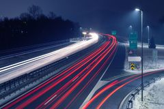 Highway at night with bright trails of light from incoming and outgoing traffic. In snowy conditions. Transportation, traffic, urbanism and infrastructure royalty free stock photos