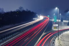 Highway at night with bright trails of light from incoming and outgoing traffic. Highway at snowy foggy night with bright trails of light from incoming and stock images