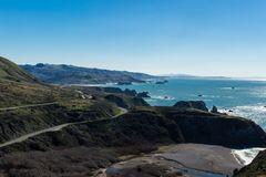 Highway one winding up the North Pacific coast. Bright blue sky and ocean. sandy beach royalty free stock image