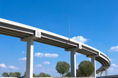 Highway overpass against blue sky. With trees below and clouds beyond Royalty Free Stock Photos