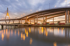 Highway overpass intersection connect to suspension bridge river front Stock Photo