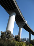 Highway overpass on pillars towers over park below Royalty Free Stock Photography