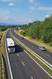 Highway passing through the countryside, truck and passenger cars Stock Image