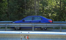 Highway railings fenced asphalt road and blue sedan on the road Royalty Free Stock Photo