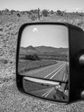 Desert Highway Reflection. A highway reflects in the side mirror of a vehicle showing the open road in a desert Royalty Free Stock Images