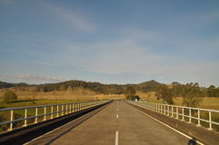 A highway road bridge tapers to green hills. This is a concrete road bridge on a country road that tapers into the distance to farmland and distant hills. to the Stock Photo
