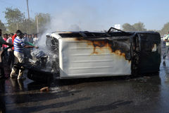 Highway Road Car Accident. On SG Highway, Ahmedabad, India on 17th March 2012 showing Mitshubishi Pajero toppled at one side and burnt in front with people Stock Photos