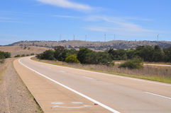 A highway road into a hill of wind generators. This is dual cariageway concrete highway, sometimes called a freeway or expressway, diappearing via a sweeping Royalty Free Stock Photography