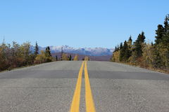 HIGHWAY ROAD LEADING TO SNOW COVERED MOUNTAINS IN FALL. Highway road leading to snow covered mountains in distance in Fall. Taken in Alaska Royalty Free Stock Image