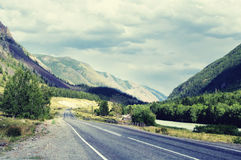 Highway road in a narrow mountain valley along the river, woodla Royalty Free Stock Photography