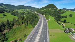 Highway road in a nature. Aerial shoot of a highway road with traffic cars and trucks in a nature full of small hills and valley stock footage