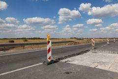 Highway or road in reconstruction. Roadworks, road signs at a highway or road on reconstruction with blue sky and clouds Stock Photo