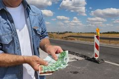 Highway or road in reconstruction, worker holding money. Roadworks, worker holding Euro money with road signs and road or highway  on reconstruction in backround Stock Image