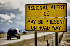 Highway road sign ice alert winter storm car truck danger Royalty Free Stock Photo