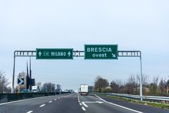 Green highway road sign to Milano and Brescia. Green highway sign to Milano straight ahead and Brescia right directions, Italy stock photography
