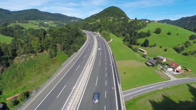 Highway road traffic on a bridge in a valley. Aerial shoot of a highway road with traffic cars and trucks in a valley with green grass field and trees in nature stock video footage