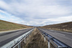 Highway road. Without traffic in daylight with cloudy sky Royalty Free Stock Images