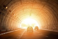 Highway road tunnel traffic car speed street with bright light at end of tunnel. Highway road tunnel traffic car speed on street with bright light at end of stock image