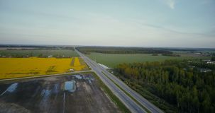 Highway road in valley with forest canola field. Aerial drone 4K shot traffic cars and trucks. Agricultural industry. Birds eye view highway road in valley with stock footage