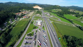 Highway roads with cars and trucks. Aerial slow motion shoot of a highway road with cars and trucks and a big parking place near the gas station stock footage