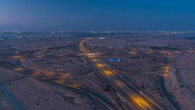 Highway roads with traffic night to day timelapse in a big city from Ajman to Dubai before sunrise. Transportation concept. Highway roads in desert with traffic royalty free stock photo
