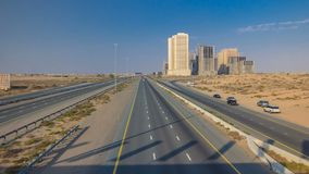 Highway roads with traffic timelapse in a big city from Ajman to Dubai before sunset. Transportation concept. Highway roads in desert with traffic timelapse in royalty free stock photos
