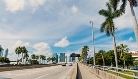 Highway or roadway with cars and skyline of miami, usa. Road with traffic signs for transport vehicles and palm trees on. Highway or roadway with cars and royalty free stock images