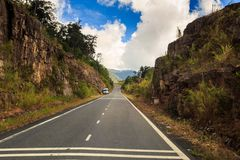 Highway between Rocky Hills Distant Bus Blue Sky. Highway between rocky hills vanishes into space against blue sky distant bus Royalty Free Stock Image