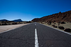 Highway in rocky landscape. Highway receding past rocky volcanic landscape on island of Tenerife, Canary Islands, Spain Stock Image