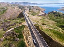 Highway scenic interstate asphalt road with cars and trucks at scenic mountain area and ocean Royalty Free Stock Photography