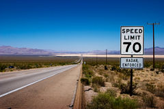 Highway sign. Desert highway to horizon with a speed limit sign on a side Stock Photography