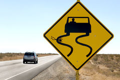 Highway Sign Humor with Speeding Car. A funny but sick sign along a desert highway Stock Photo