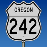 Highway sign for Route 242 in Oregon. A 3d rendering of a highway sign for the Old McKenzie Pass Route 242 with blue sky Stock Photo