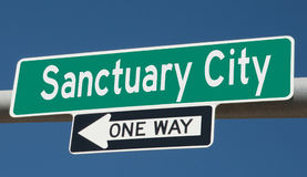 Highway sign with SANCTUARY CITY and ONE WAY Stock Image