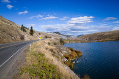 Highway skirting a scenic mountain lake. Tarred highway skirting a scenic tranquil blue mountain lake under a cloudy blue sky in mountainous terrain stock photography