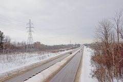 Highway through a snow covered landscape in Gatineau, Quebec. Highway through a snow covered landscape on a cold grey winter day in Gatineau, Quebec stock photo