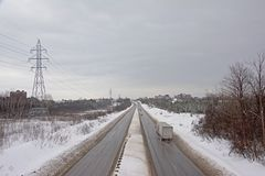 Highway through a snow covered landscape in Gatineau, Quebec. Highway through a snow covered landscape on a cold grey winter day in Gatineau, Quebec stock image