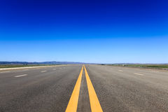 Highway in steppe against a blue sky. Long road stretching out into the distance Stock Photos