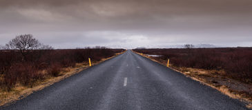 Highway straight road leading to the snowy mountains Stock Photos