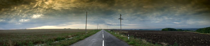 Highway stretching out into the farming fields. Under the dramatic sky Stock Photo