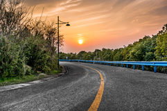 Highway sunset. A red sunset in the outskirts of the road, the sun was setting Royalty Free Stock Photos