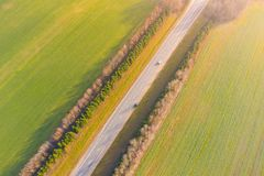 Highway surrounded by green fields in autumn. Aerial landscape. Drone view royalty free stock image