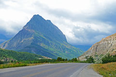 Highway surrounded by mountains in Glacier National Park. Stock Photos