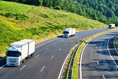 Highway with three oncoming white truck in a woode Royalty Free Stock Images