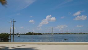Highway to Key West Florida. View of old abandoned bridge and coast line of Atlantic ocean on blue sky.