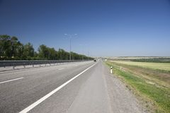 Highway to the left of the fence In a blurred background, cars are coming stock photos